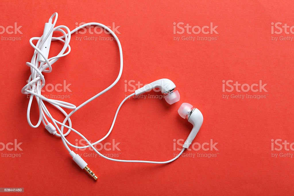 White headphones on a red paper background stock photo