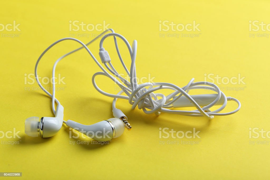 White headphones on a yellow paper background stock photo