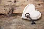 White heart  and an old key on rustic wooden board