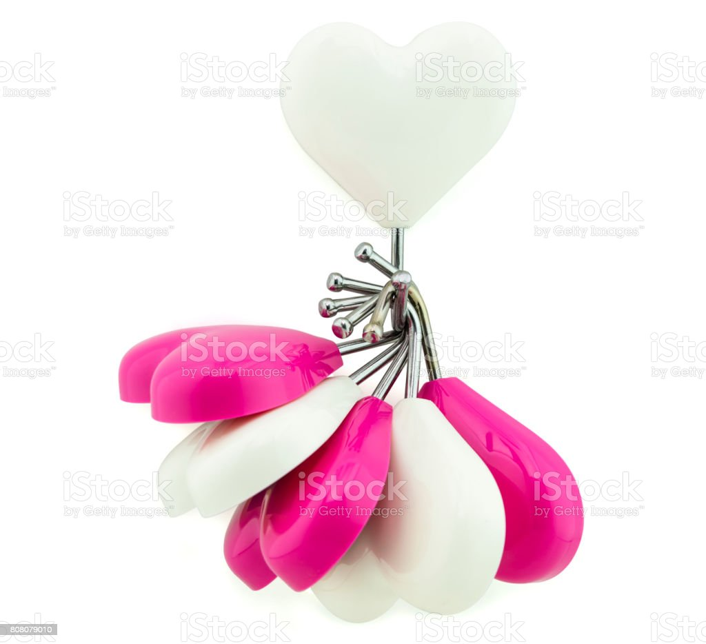 White heart magnet hook hanging white and pink hearts isolated on white, business concept as leadership stock photo