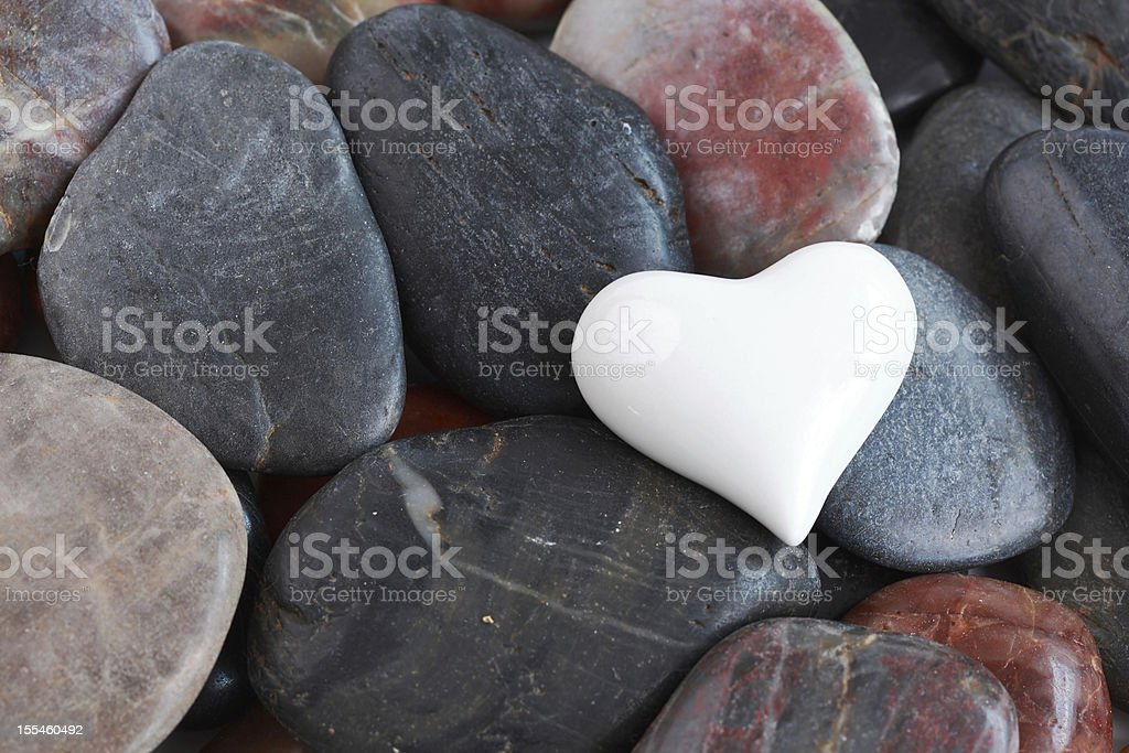 White heart surrounded by stones stock photo