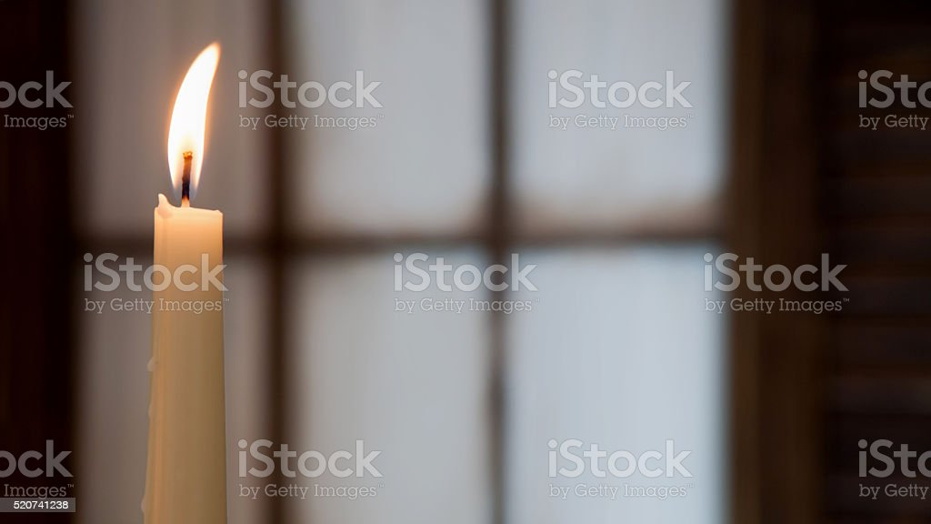 White high burning candle on a blurred background of  window stock photo