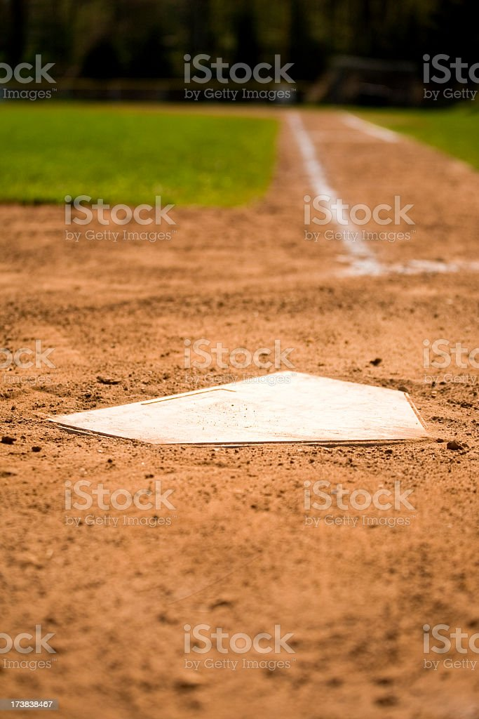 A white home plate on a baseball field stock photo
