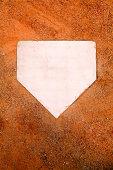 White home plate set in orange sand