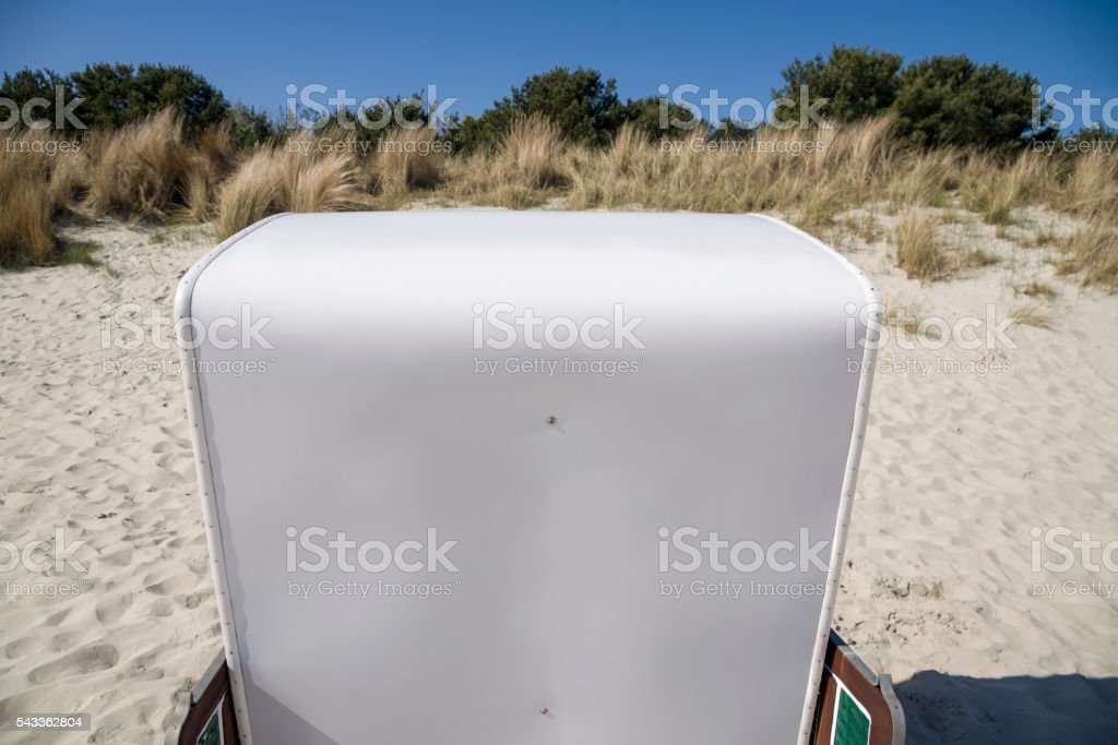 White hooded beach chair and sand dune stock photo