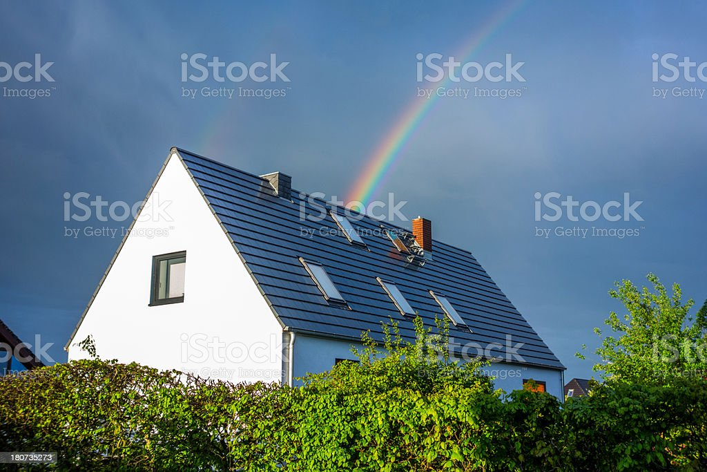White house with rainbow in the sky coming over tiled roof royalty-free stock photo