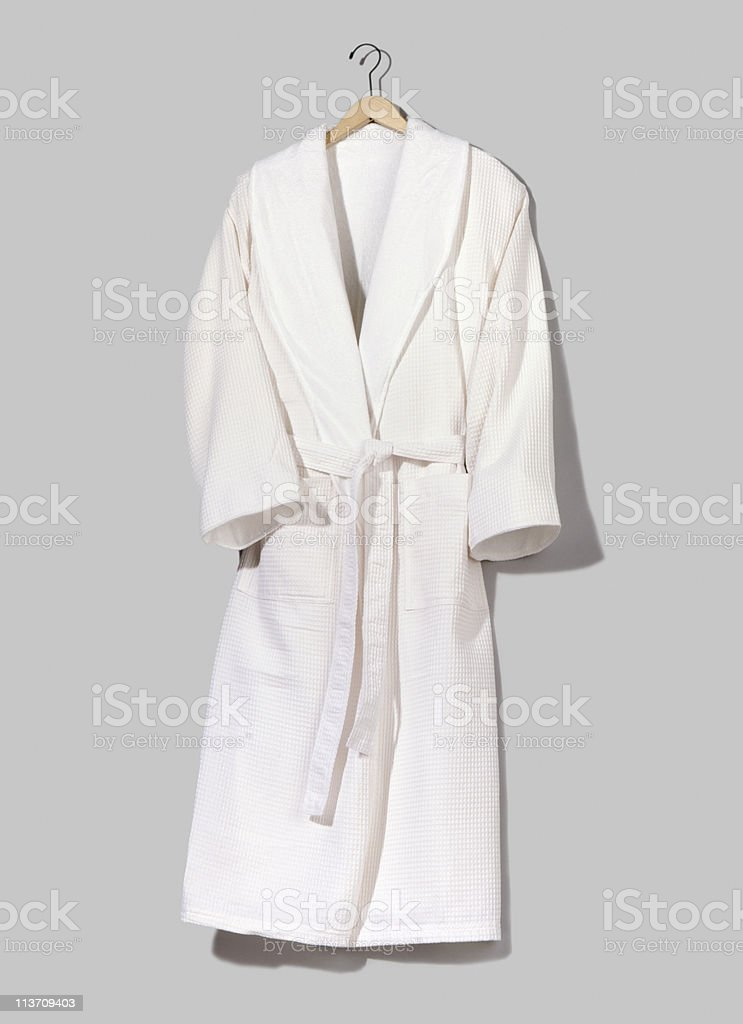 A white hung up bathrobe on a grey wall stock photo