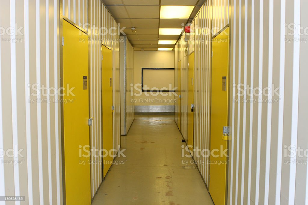 White industrial corridor with yellow numbered doors royalty-free stock photo