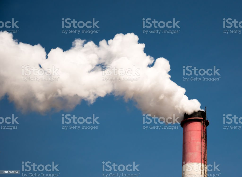 white industrial smoke from the chimney on a blue sky stock photo
