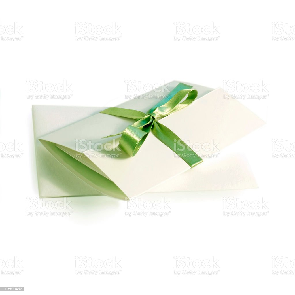A white invitation folded and with a green ribbon royalty-free stock photo