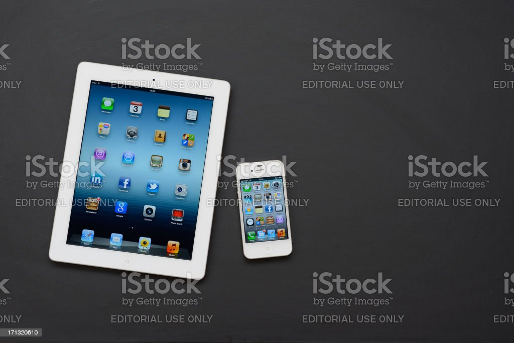 White iPad 3 & iPhone 4 on blackboard royalty-free stock photo
