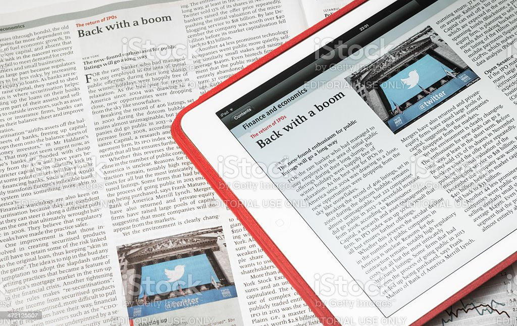 White iPad Air and The Economist magazine displaying same article stock photo