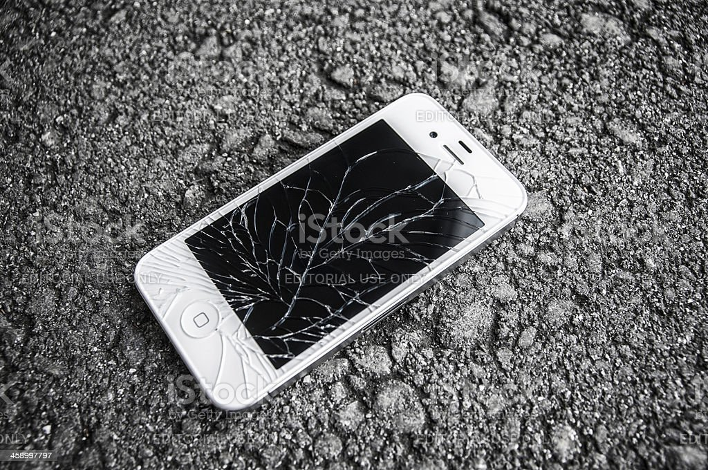 white iPhone 4s with broken retina display laying on asphalt stock photo