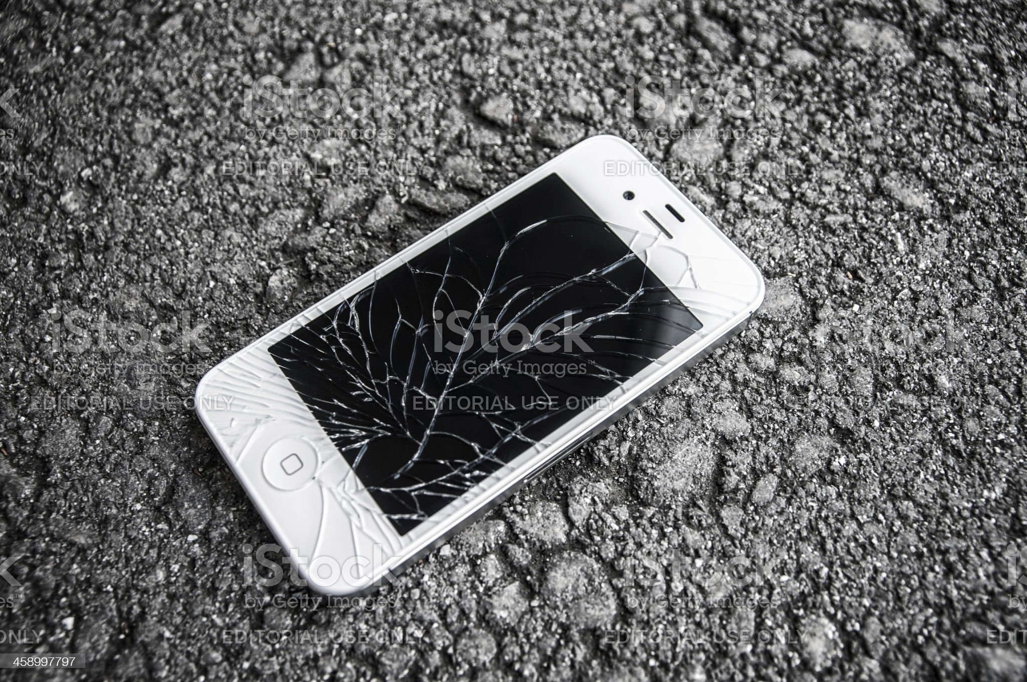 white iPhone 4s with broken retina display laying on asphalt royalty-free stock photo