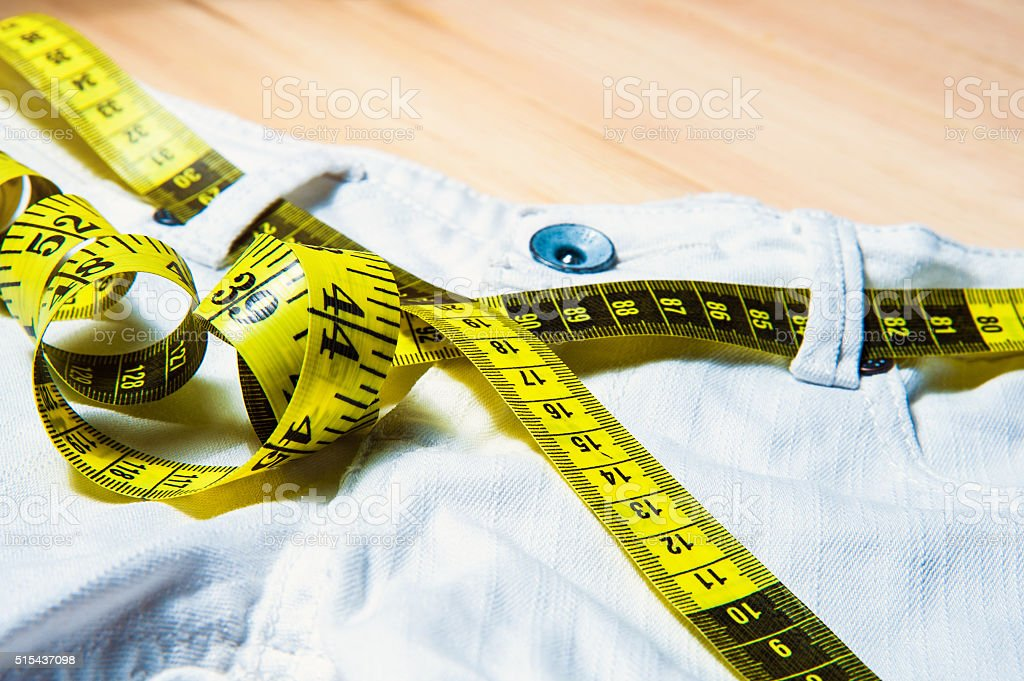 White jeans and measuring tape on wooden background stock photo