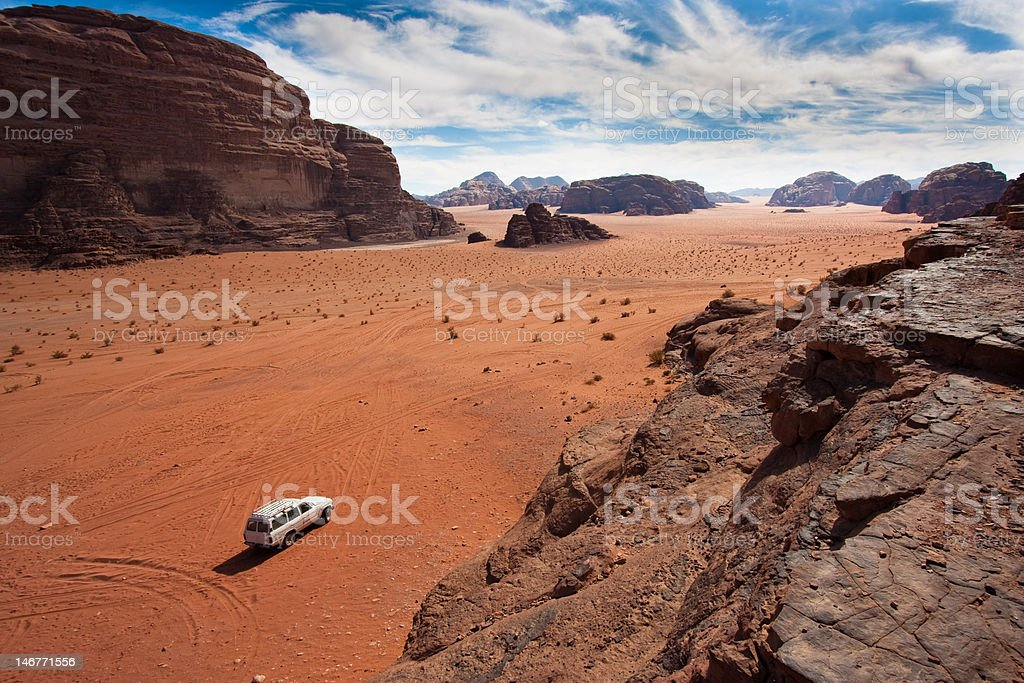 White jeep between the mountains in Wadi Rum, Jordan. stock photo