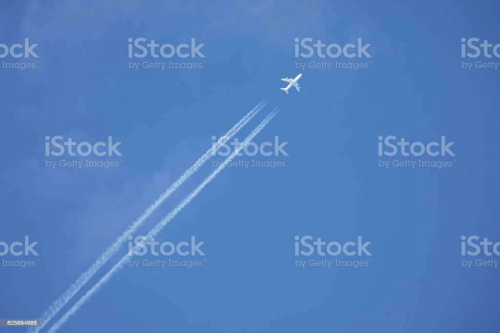 white jet airplane flying high in the blue sky stock photo
