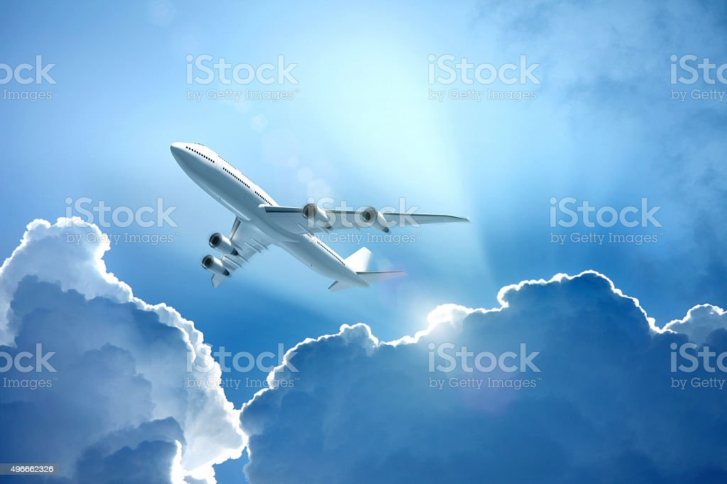 White jet airplane flying over the clouds with sun beams stock photo
