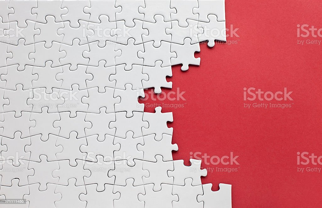 White jigsaw puzzle on a red background stock photo