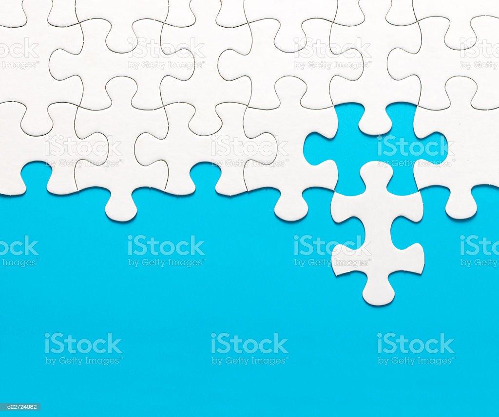 White jigsaw puzzle on blue background stock photo