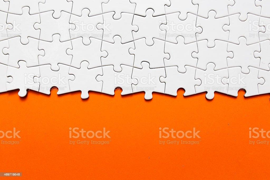A white jigsaw puzzle with orange background stock photo