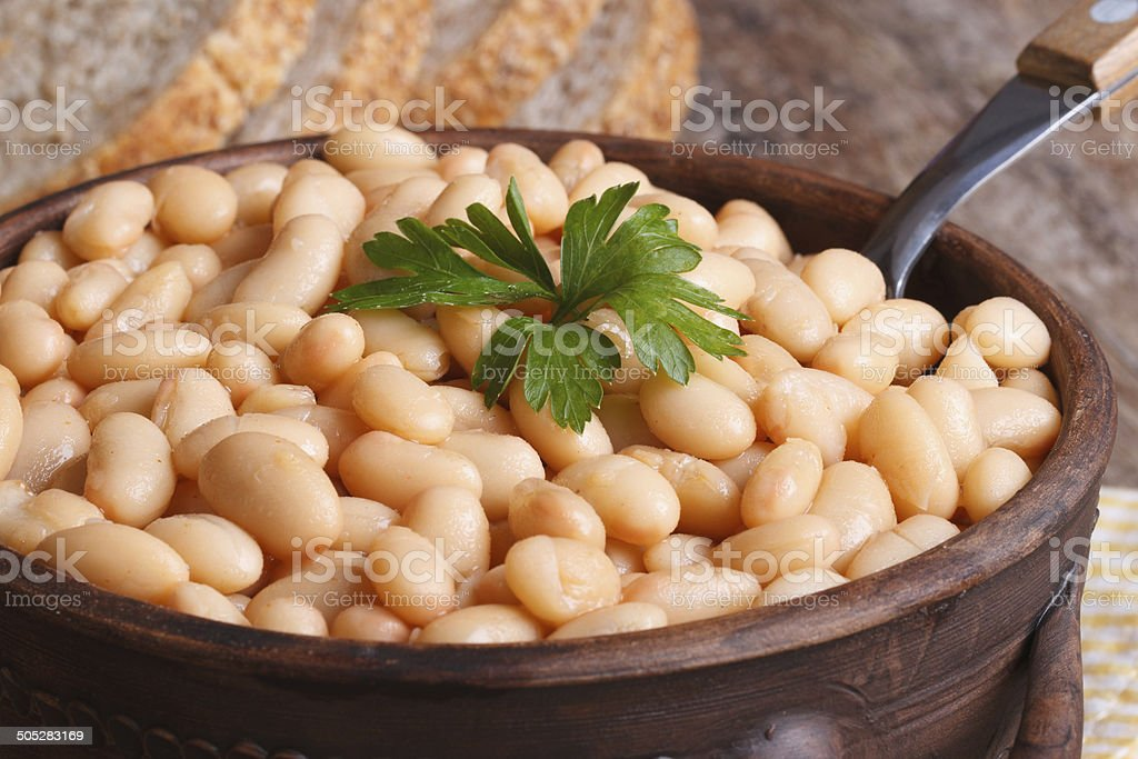 white kidney beans in a brown pot macro and bread stock photo
