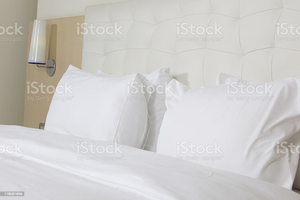 White kind sized bed in luxury hotel room with fluffy pillow stock photo