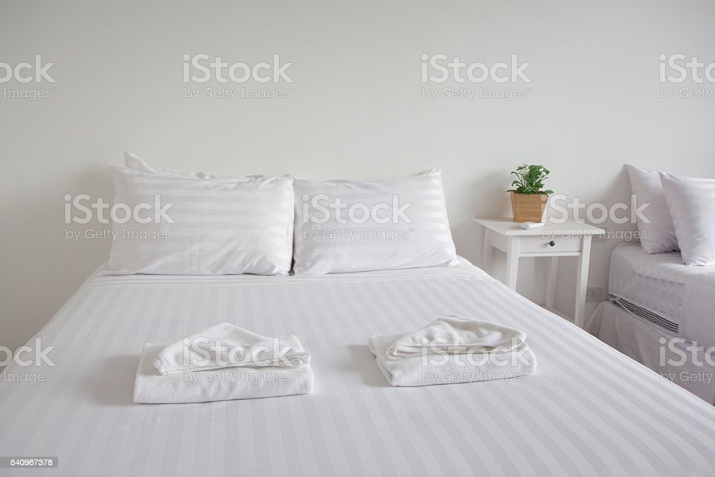 white king size bed, two pillows, pot plant in bedroom Стоковые фото Стоковая фотография