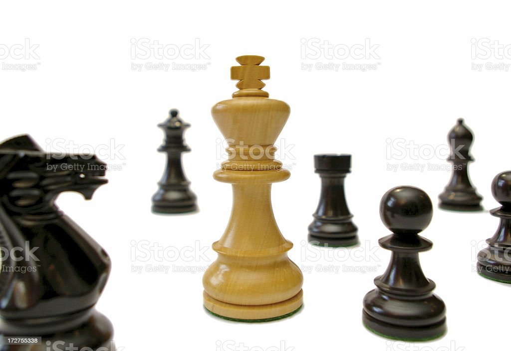 White king surrounded by black chess pieces royalty-free stock photo