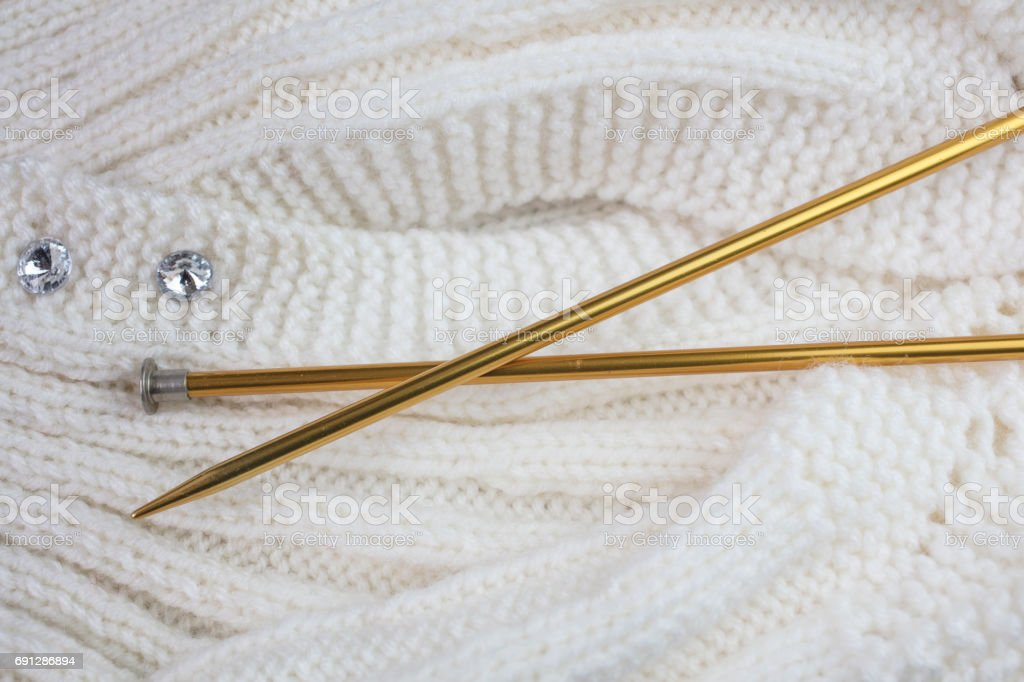 White knitted garment with gold colored knitting needles stock photo