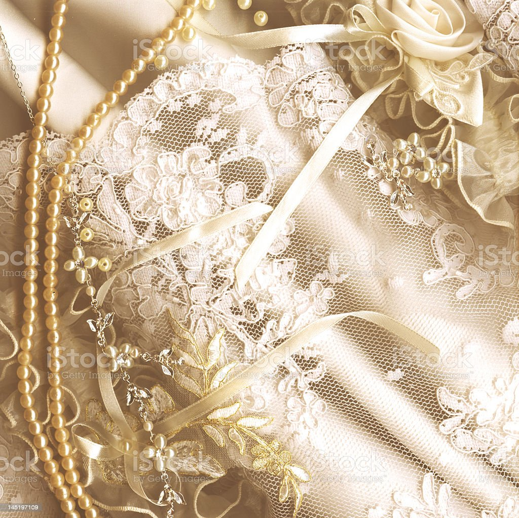 White lace and pink silk fabric with pearls necklace on it stock photo