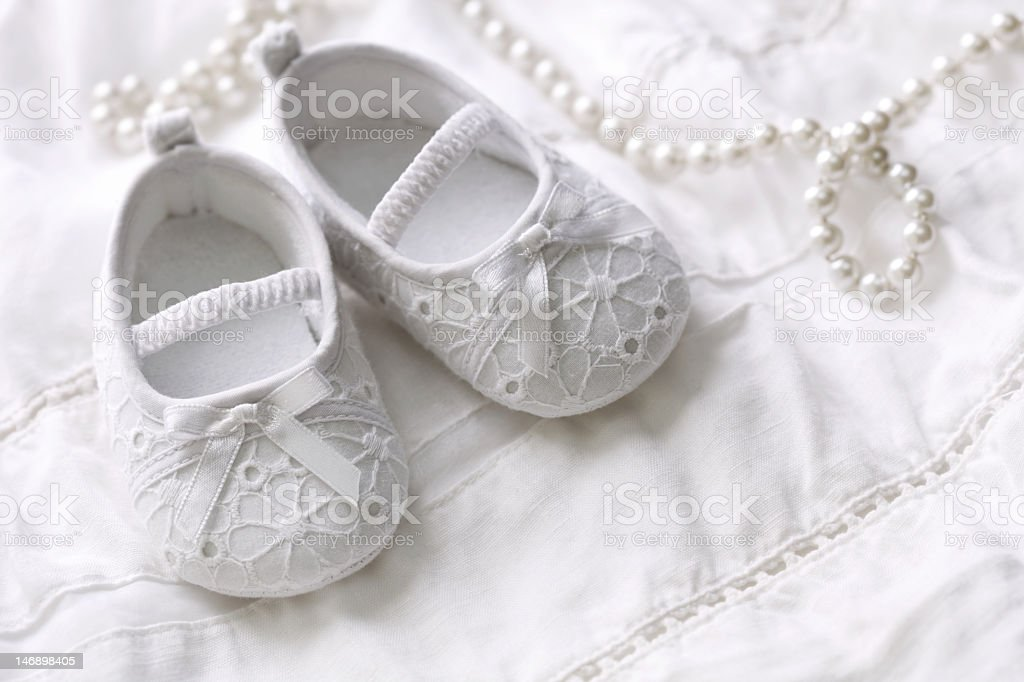 White lace children's baptism slippers on white gown stock photo