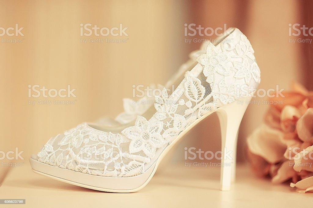 White lace wedding shoe and orange flowers stock photo