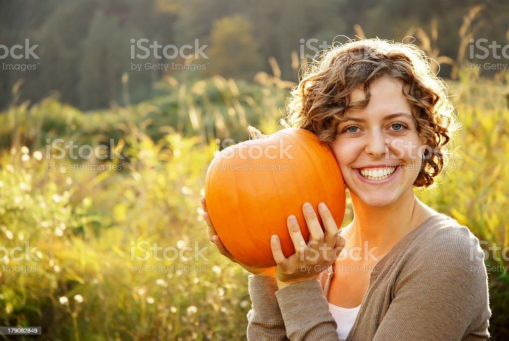 A white lady holding a pumpkin stock photo