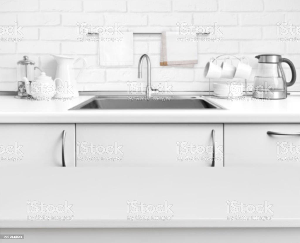 White laminated table on blurred rustic kitchen sink interior background stock photo