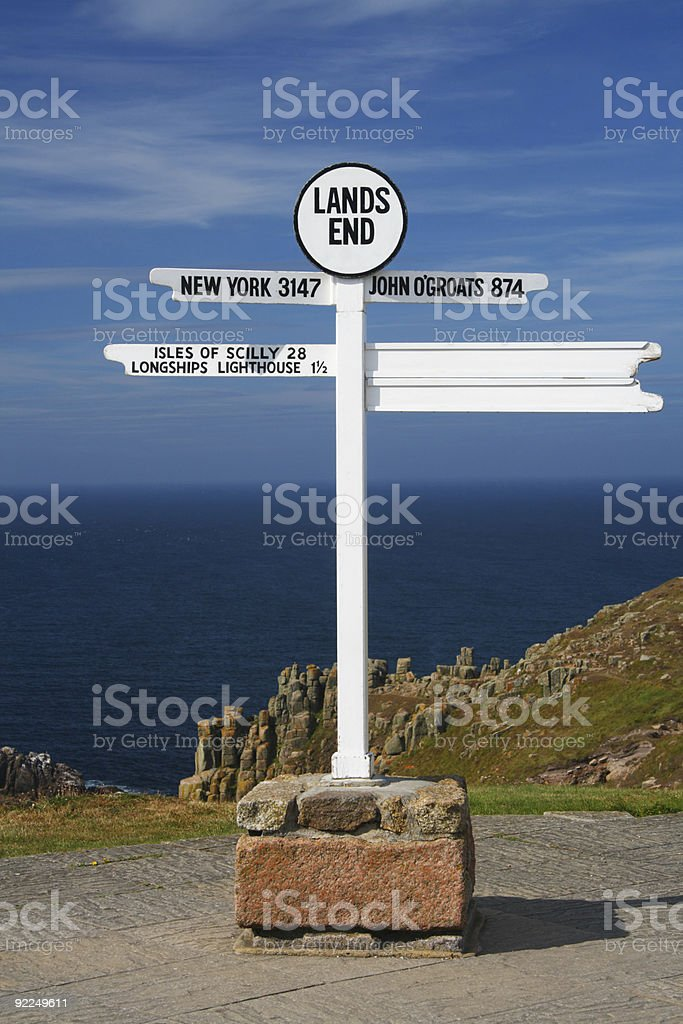 white Land's end directional sign over sea and cliffs background stock photo