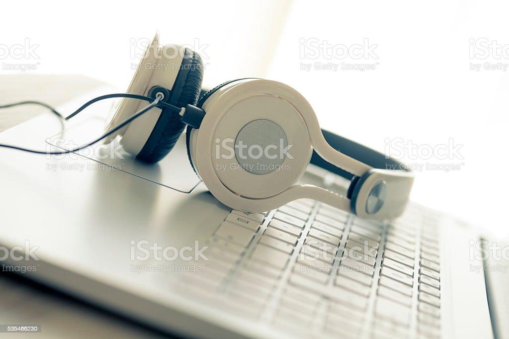 White laptop and headphones stock photo