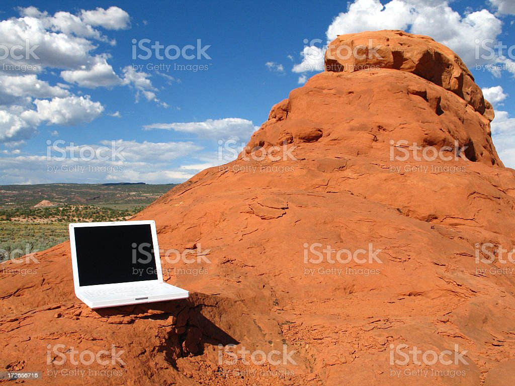 White Laptop Computer on Desert Red Rock Formation in Utah royalty-free stock photo