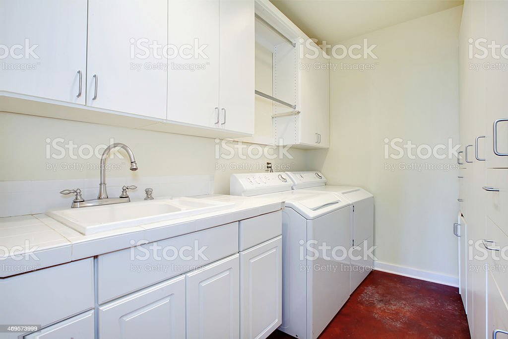 White laundry room with a red floor stock photo