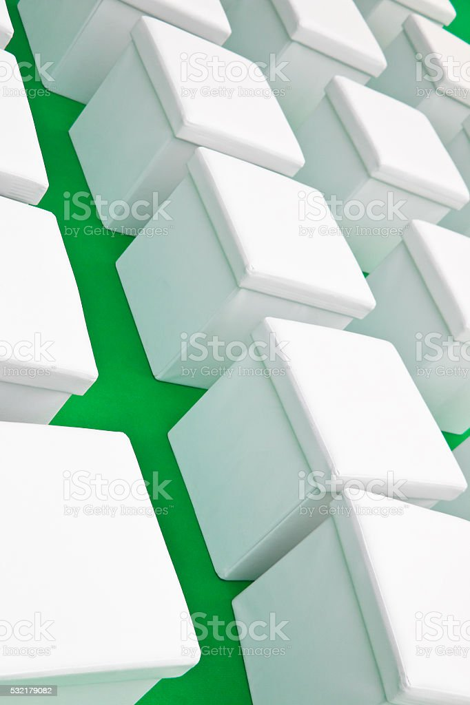 White leather cubes on green background stock photo