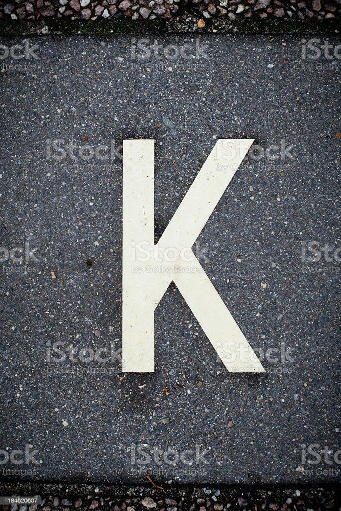 White Letter K on the Road Asphalt. royalty-free stock photo