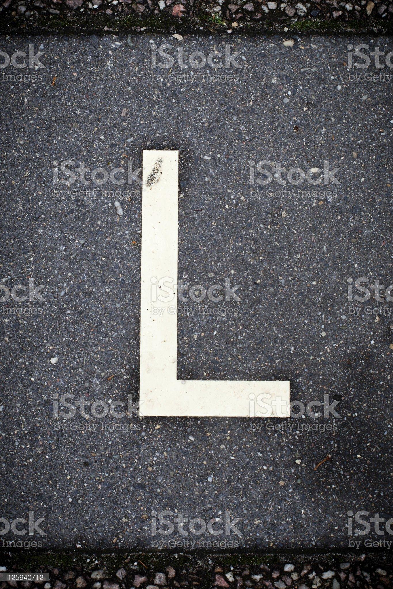 White Letter  L on the Road Asphalt. royalty-free stock photo