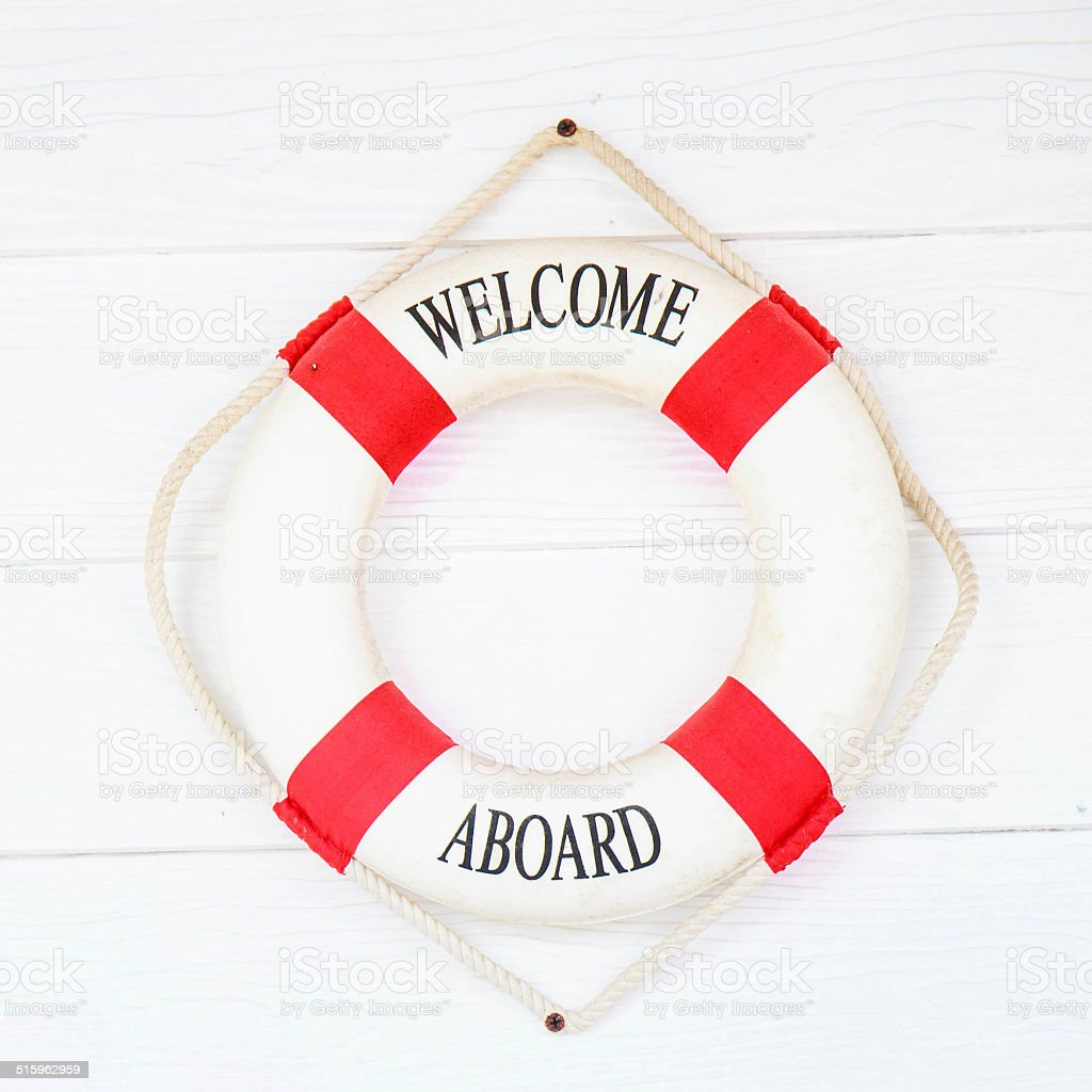 White Life buoy with welcome aboard on white wall stock photo
