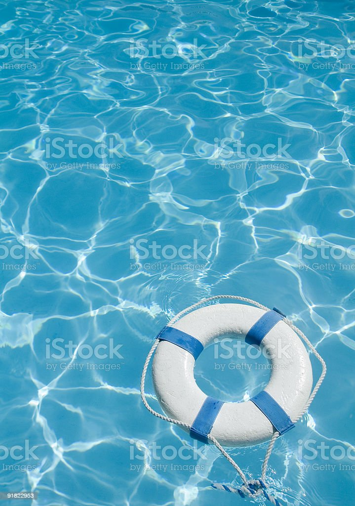 A white life preserver floating in a pool's blue water stock photo