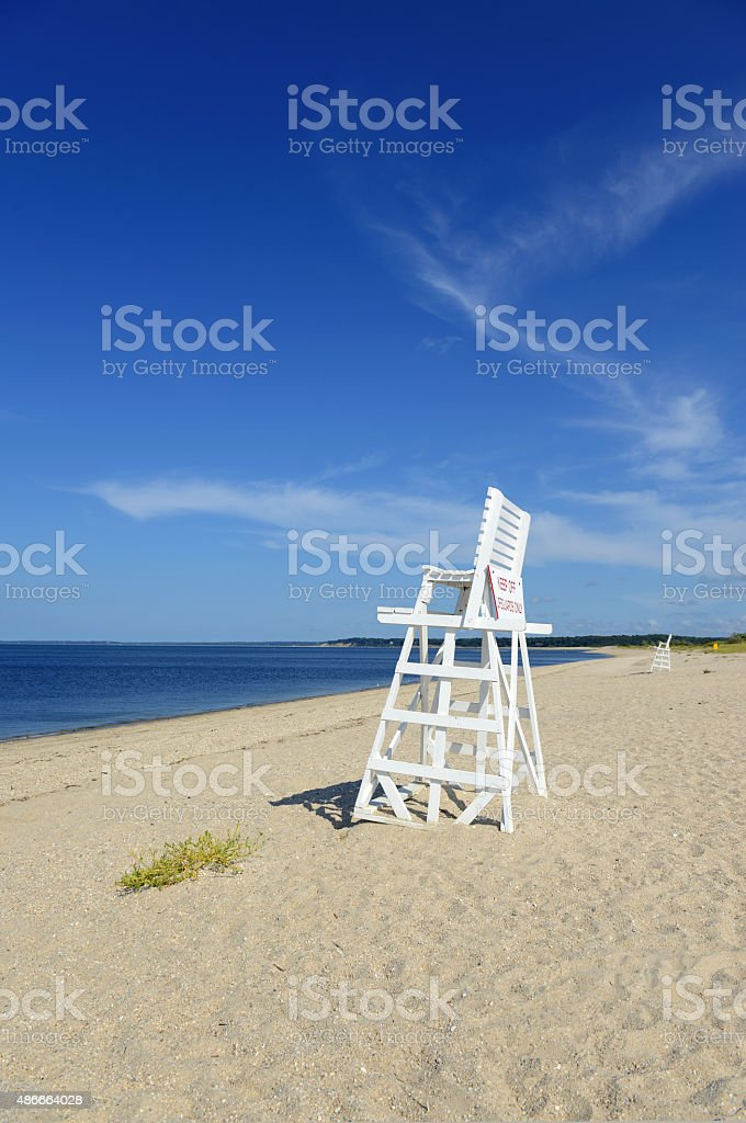 White lifeguard chair on empty sand beach with blue sky stock photo