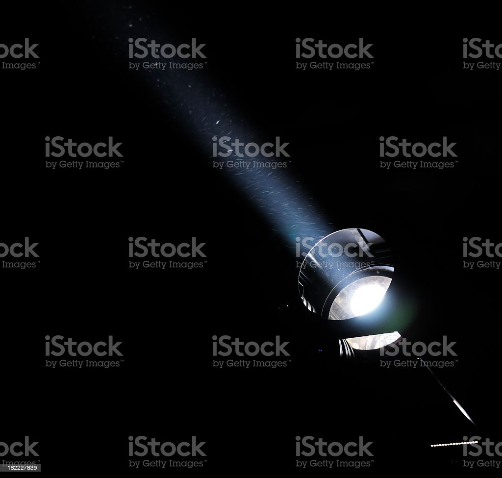 A white light beam shining through the darkness stock photo