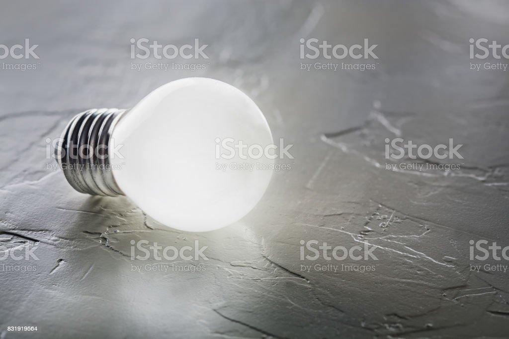 White light bulb glowing on concrete background, idea concept stock photo
