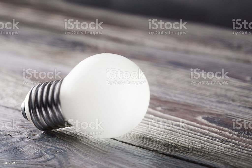 White light bulb glowing on wooden background, idea concept stock photo
