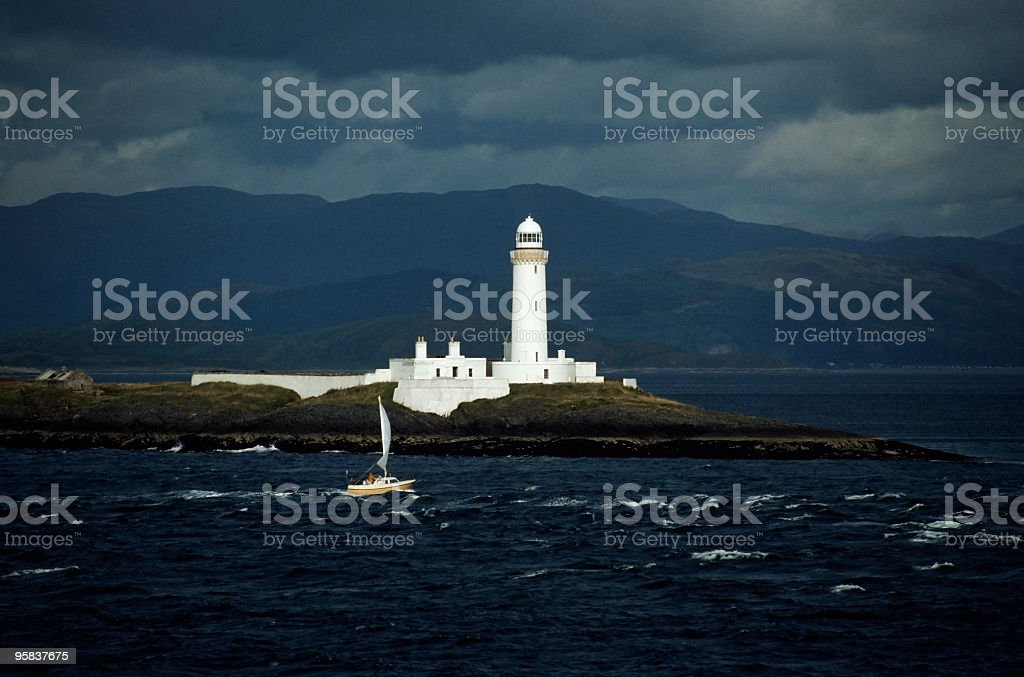 White lighthouse and sail boat at sunset royalty-free stock photo