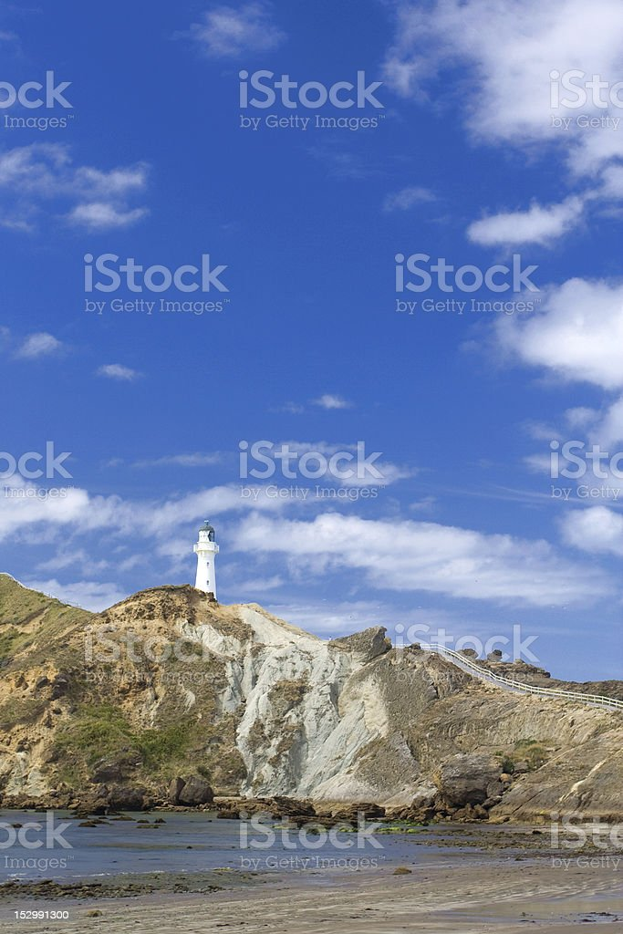 white lighthouse on a cliff stock photo
